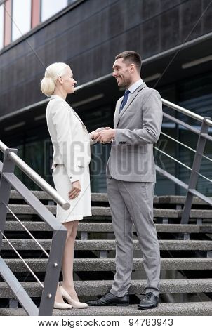 business, partnership, success, gesture and people concept - smiling businessman and businesswoman shaking hands on city street