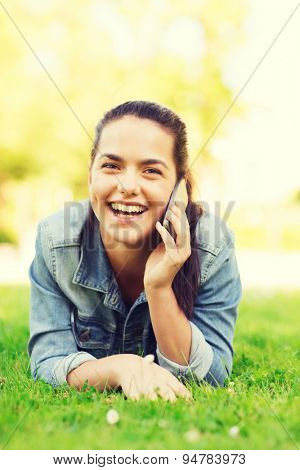 lifestyle, summer vacation, technology, leisure and people concept - laughing young girl with smartphone talking and lying on grass in park