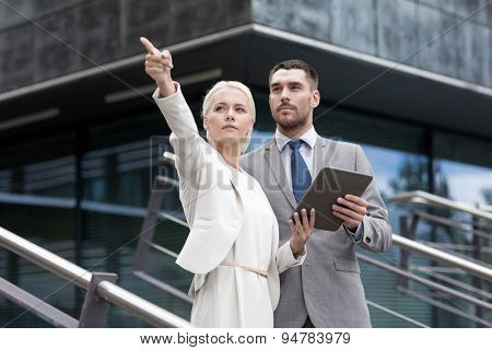 business, partnership, technology and people concept - serious businessman and businesswoman with tablet pc computer over office building