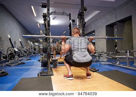 sport, fitness, bodybuilding, lifestyle and people concept - young man with bar flexing muscles in gym