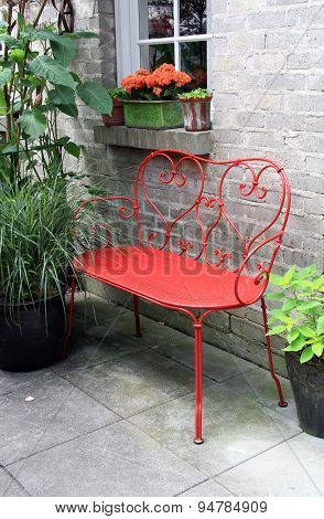 Red wrought iron bench outside on a garden patio.