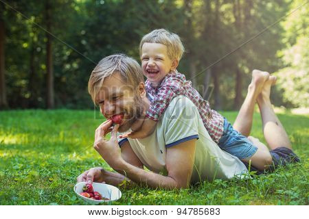 Young father and his son eating strawberries in Park. Picnic. Outdoor portrait