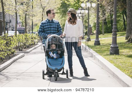 young family with baby strollers on city walk