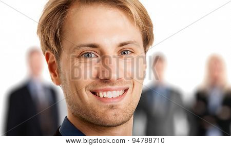 Portrait of a young smiling businessman in front of his team