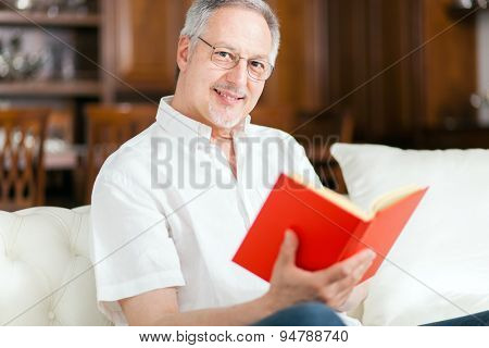Happy mature man reading a book