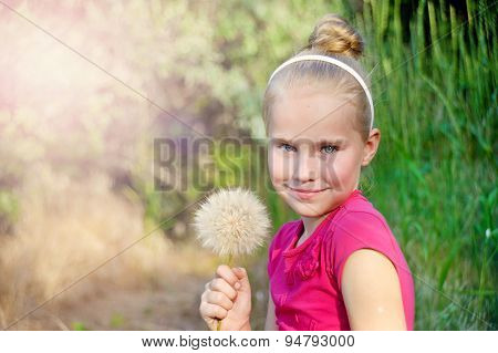 Cute little girl  with dandelion on the meadow in spring day