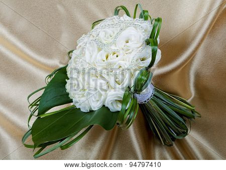 Wedding Bouquet Of The Bride Against A Golden Fabric