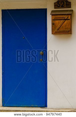 Blue entrance door on cement colored building