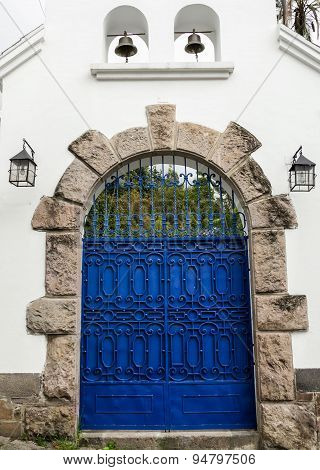 Artsy blue painted double gate with grey stones forming an arch on white concrete building