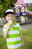 picture of licking  - Cute little boy smiling and licking his ice cream at an outdoor carnival - JPG
