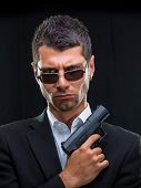 stock photo of handgun  - Portrait of a man in suit with handgun - JPG