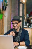 stock photo of internet-cafe  - Fashionable and stylish young man relaxing with coffee music and internet browsing at the cafe bar. Selective focus. Toned image ** Note: Visible grain at 100%, best at smaller sizes - JPG