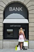 picture of automatic teller machine  - Girl with shopping bags at ATM - JPG