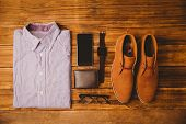 stock photo of loafers  - Shirt shoes glasses next to wallet and smartphone on wooden table - JPG