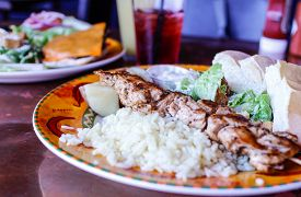foto of souvlaki  - Chicken souvlaki with rice on pretty table  - JPG