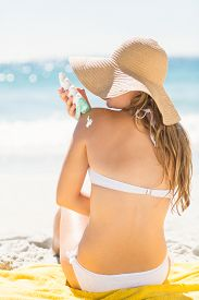 image of sun tan lotion  - Pretty blonde woman putting sun tan lotion on her shoulder at the beach - JPG