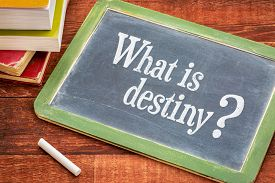 stock photo of slating  - What is destiny question on a slate blackboard with a white chalk and a stack of books against rustic wooden table - JPG