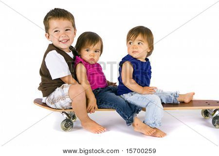Little boy and his twin sisters on a skateboard