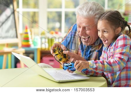 Portrait of grandfather and granddaughter play videogame on laptop