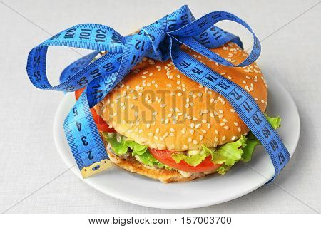 Dieting concept. Plate with tasty hamburger and measuring tape on light background