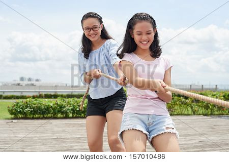 Cheerful Asian girls playing tug of war