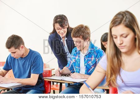 Smiling teacher supervises her student's test and smiles