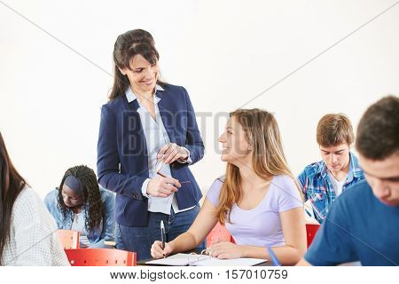 Teacher supervises her student's exam and they both smile