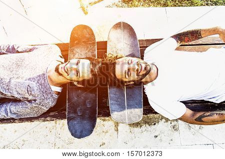 Best skaters friends having fun and smiling together outdoor - Young cheerful people looking the sky with skateboard under the head - Upside down point of view - Happy friendship concept - Warm filter