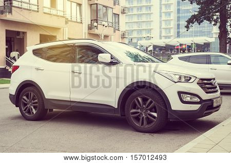 Sochi, Russia - October 11, 2016: New white Hyundai Santa Fe parked on the street of modern tile Sochi City.