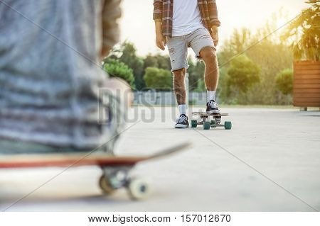 Two skateboarders training in skate park at sunset - Close up of young tattoo man training with longboard in city urban contest - Extreme sport concept - Warm vintage filter - Focus on right feet