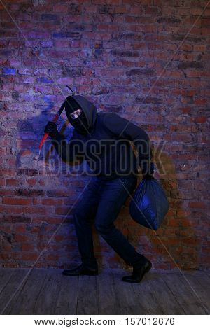 Crook near wall with bag