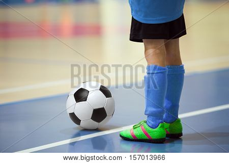 Football futbal training for children. Indoor soccer young player with a soccer ball in a sports hall. Player in blue uniform. Sport background.