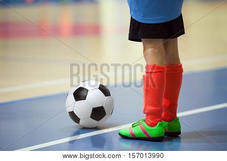 Football futsal training for children. Indoor soccer young player with a soccer ball in a sports hall. Player in blue and red uniform. Sport background.