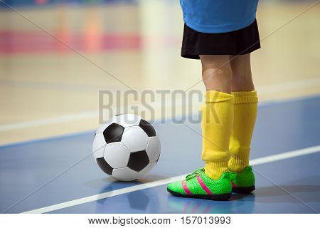 Football futbal training for children. Indoor soccer young player with a soccer ball in a sports hall. Player in blue and yellow uniform. Sport background.