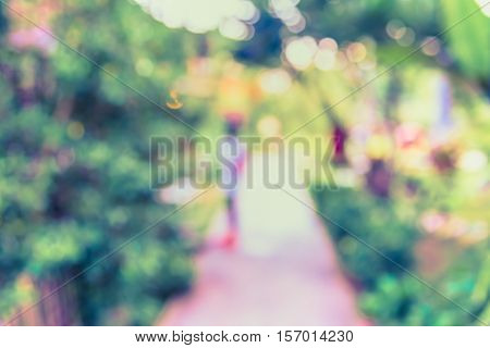 vintage tone Abstract blur image of walk way with people in green garden for background usage.