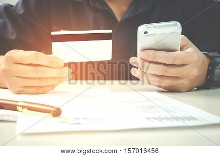Man Holding Credit Card And Using Cell Phone