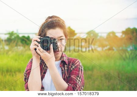 young woman photographer taking at park in holiday