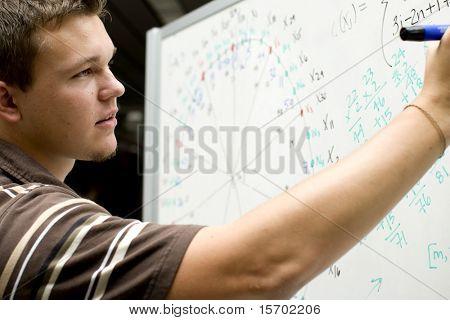 Jovem na escola fazendo uma equação matemática
