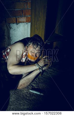 Bounded Man with mouth covered by masking tape lying in dark basement.