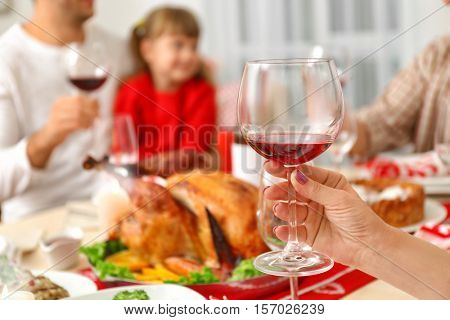Female hand holding glass with red wine on blurred background, close up view
