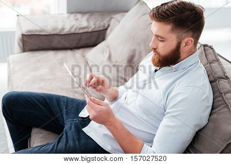 Man with tablet on sofa. side view