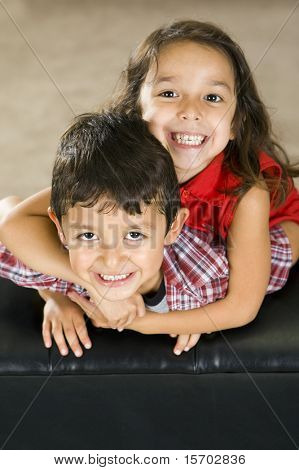 Cute brother and sister sitting on a couch