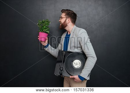 Profile of happy bearded young man in glasses with flowers in pot and turntable