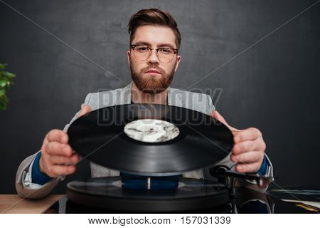 Portrait of bearded young man in glasses using turntable and vinyl record