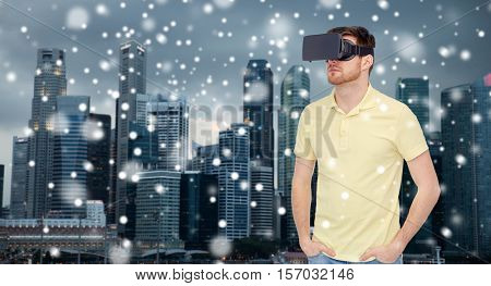technology, augmented reality, travel, entertainment and people concept - young man with virtual headset or 3d glasses over singapore city skyscrapers background over snow