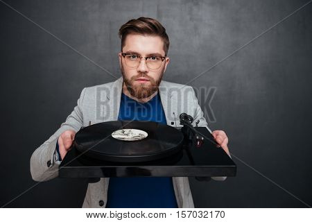 Serious bearded young man in glasses holding turntable