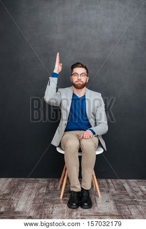 Amusing bearded young man geek in glasses sitting with raised hand
