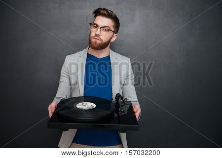 Handsome bearded young man in glasses syanding and holding turntable