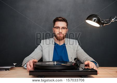 Serious bearded young businessman in glasses with turntable on his table