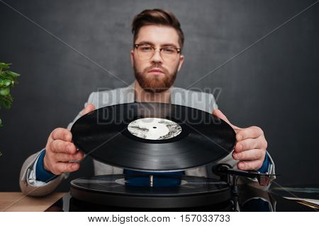 Serious bearded young man in glasses using turntable and vinyl record